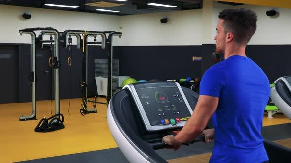Thumbnail for A Young Fit Man Walks on a Treadmill in a Gym - Closeup From Behind