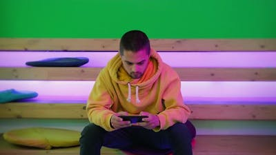 Male Gamer Using Mobile Phone for Video Game