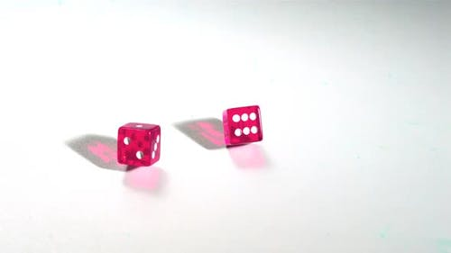 Pink dice rolling on white surface