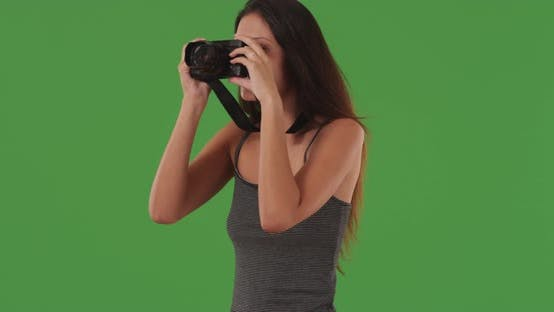 Thumbnail for Young female photographer taking pictures with digital camera on greenscreen