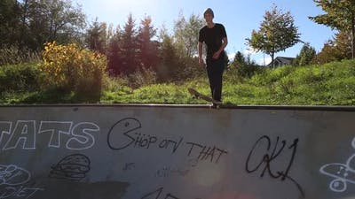 A young skateboarder skating in the bowl of a skate park.