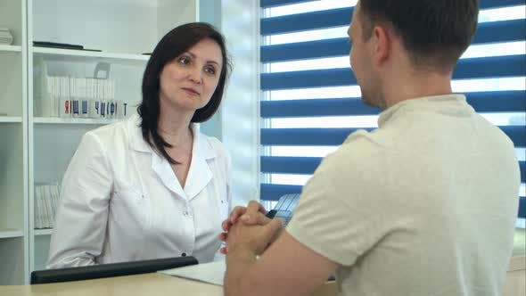 Thumbnail for Male Patient Talking with Nurse at Reception Desk in Hospital