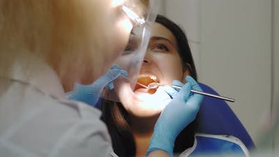 Dentist Examining a Patient's Teeth in the Dentist Office