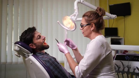 Woman Dentist Examining Patient's Teeth in Clinic
