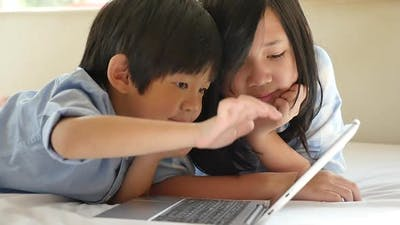 Cute Asian Children  Lying In Bed And Using Laptop On White Bed