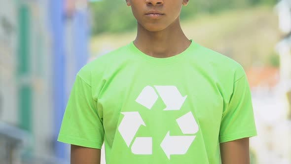 Serious boy in shirt with recycle sign promoting reusable products