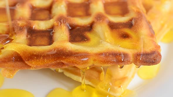 Zubereitung von Waffeln. Waffeln werden mit Honig gewässert.