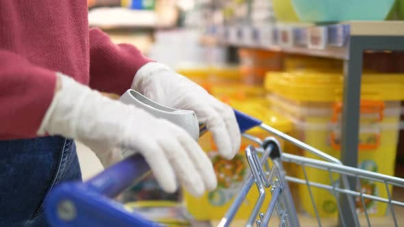 Thumbnail for Girl in Rubber Gloves Takes Hold of Handle Trolley in Rubber Gloves in Supermarket Close-up Slow