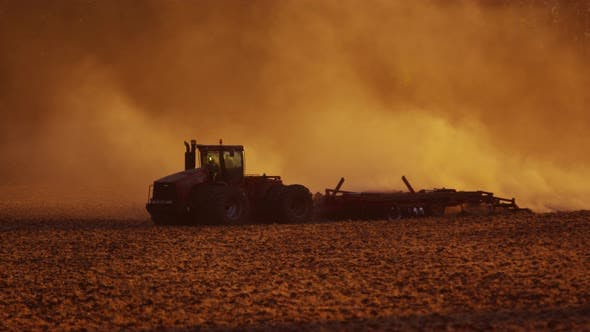 Tractor plowing field at sunset.