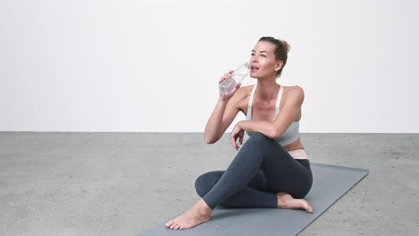 Woman Drinking Water on Exercise Mat