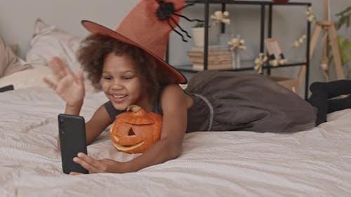 Little Witch Taking Selfie with Pumpkin