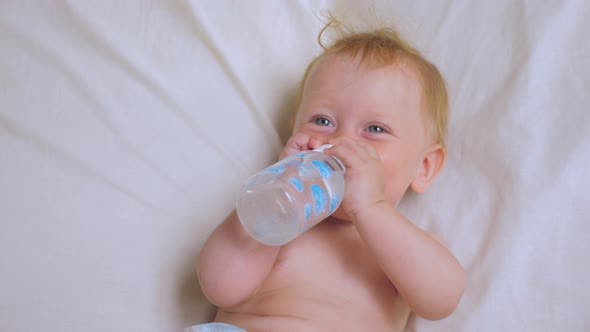 Baby girl drinking water from bottle. Nutrition for babies.