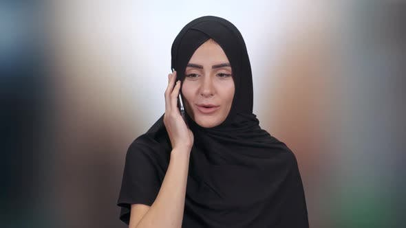 Portrait of a Beautiful Muslim Woman, a Female in a Hijab Communicates and Talks on a Mobile Phone