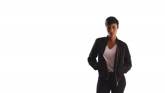 Thumbnail for Portrait of trendy black woman posing with hands in jacket pockets in studio