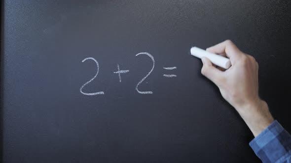 Professor writing on blackboard mathematical formulas with chalk. 2+2=4