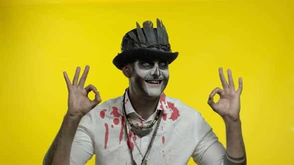 Sinister Man with Horrible Halloween Skeleton Makeupmaking Faces, Looking at Camera, Showing Ok Sign