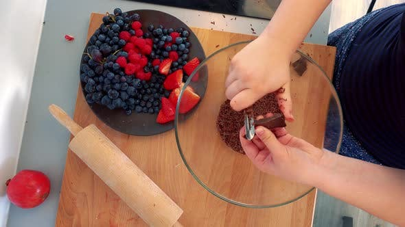 Thumbnail for A Woman Grates a Bar of Dark Chocolate Into a Glass Bowl Next To a Bowl of Fruit - Closeup