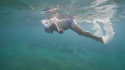 Underwater View of Senior Man in Snorkeling Mask Diving Into the Sandy Seabed.