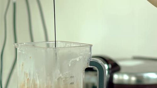 Cook Pours Hot Chocolate Into the Mixer with a Cocktail