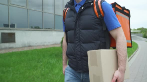 Courier with a Thermo Bag Delivers Food To the Office, the Process of Food Delivery, Man Delivers a