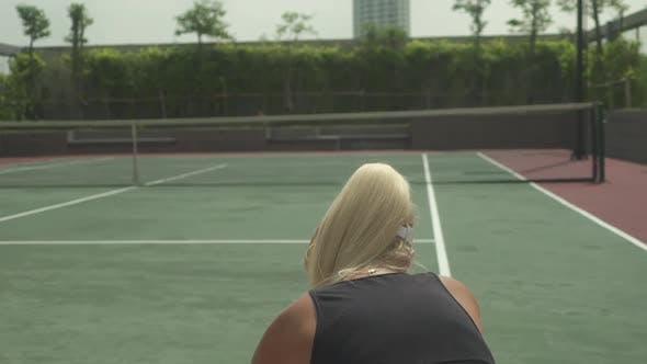 Blonde Tennisspielerin Aufstehen, nachdem sie nach einem Tennisball gegriffen hat
