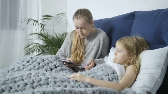 Thumbnail for Mom Checking Teen Daughter's Temperature in Bed