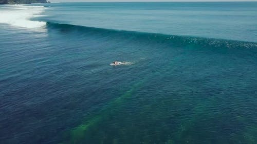 Amazing Aerial Shot of a Professional Surfer Riding a Seamless Barreling Waves.