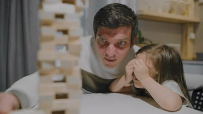 Father and Daughter are Playing a Board Game Made of Wooden Blocks
