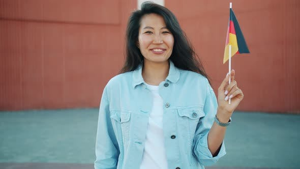 Slow Motion Portrait of Cheerful Asian Woman Holding German Flag Outdoors