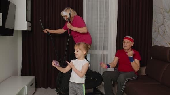 Thumbnail for Senior Couple Using Orbitrek Doing Dumbbells Exercises Child Girl Making Selfie on Mobile Phone