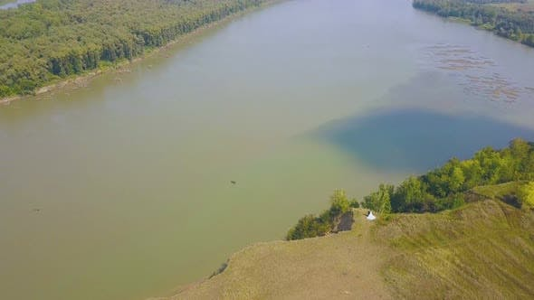Thumbnail for Just Married Couple on Steep Riverbank on Sunny Day Aerial