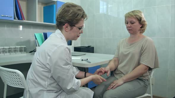 Thumbnail for Neurologist Testing Knee Reflex on a Female Patient Using a Hammer