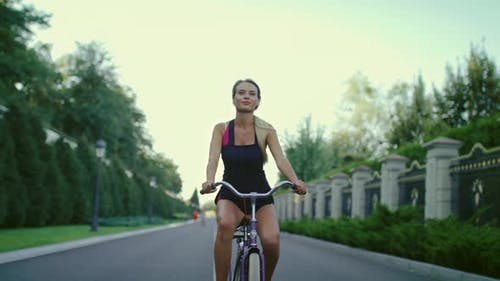 Athlete Woman Riding Bicycle in Summer Park. Sport and Active Lifestyle