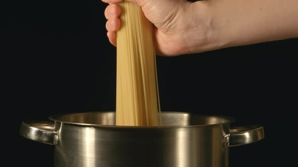 Thumbnail for A cook puts down a bunch of spaghetti in a steel pot