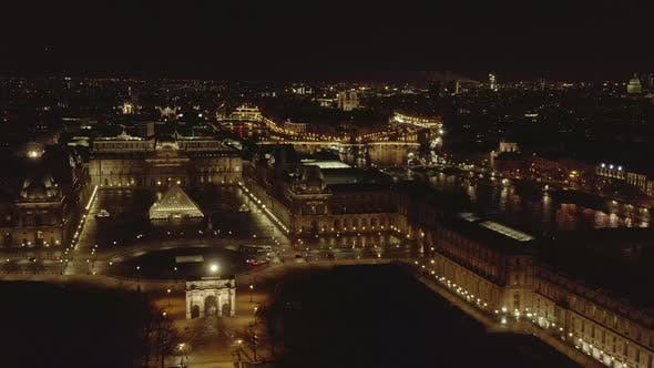 Thumbnail for AERIAL: Flight Over Glowing Louvre Museum,Pyramid and Seine River at Night in Paris, France