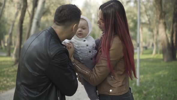 Thumbnail for Positive Caucasian Parents Playing with Cute Little Boy Outdoors