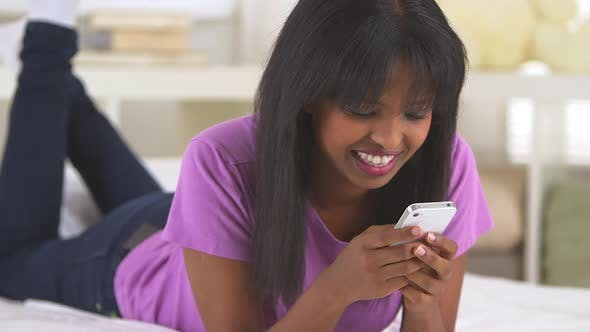 Cover Image for Black girl using smartphone and smiling