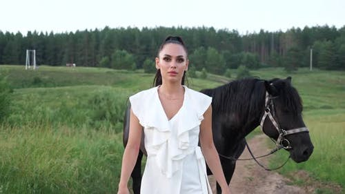Young Woman Walks and Black Stallion with Bridle Follows