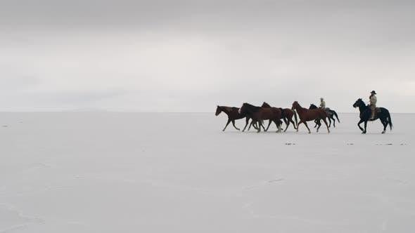 Thumbnail for Horses running with cowboys riding across salt flats