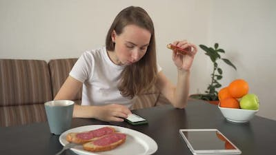 Woman Using a Smartphone at Home in a Modern Kitchen