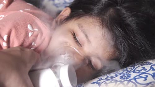 A Child Girl Sleeping on Bed While Taking Nebulizer