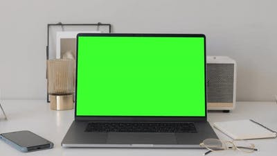 Modern laptop macbook pro with mock up chroma key green screen on table of living room