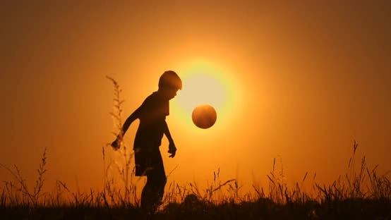 Cover Image for Little Boy Football Player Silhouette, Practicing with the Ball, the Sunset Golden Hour, Slow Motion