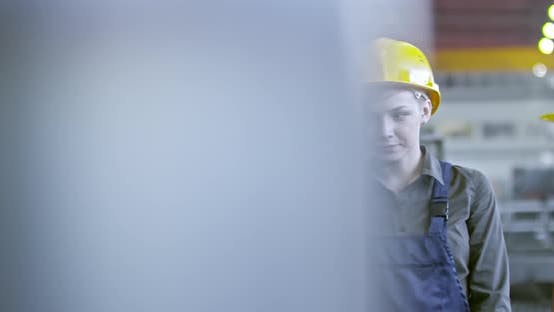 Thumbnail for Experienced Female Factory Technician Teaching Young Employees