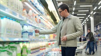 Man Buying Dairy Products in the Supermarket