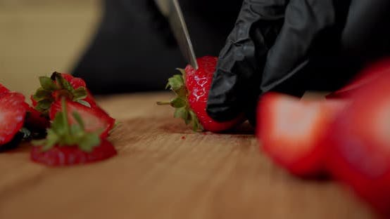 Thumbnail for Chef in Black Gloves Slicing Fresh Strawberry on Wooden Cutting Board. Close Up
