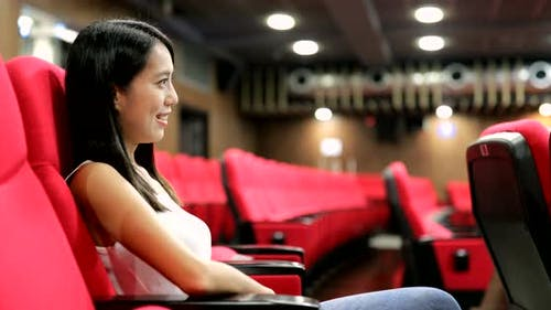 Woman Watching Talk Show in Theater