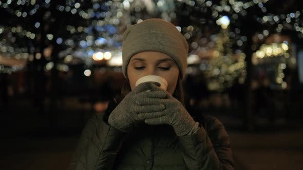 Thumbnail for Beautiful Smiling Young Woman with Natural Make Up Holds a Cup with Hot Coffee or Tea Wine Evening