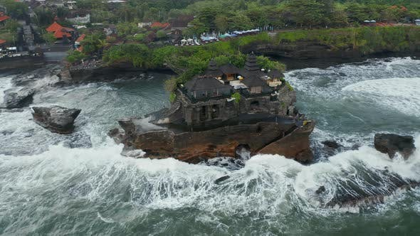 Overhead Aerial Rotating View of Stunning Buildings in Tanah Lot Temple on a Dark Ocean Cliff in