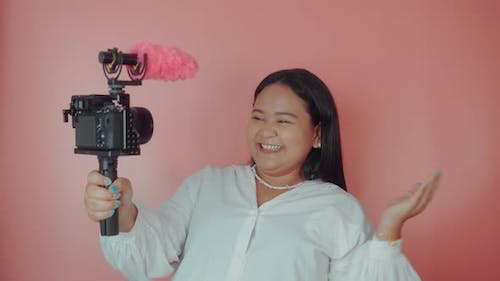 Young Woman Vlogger Recording Broadcast in Slow Motion on a Pink Background
